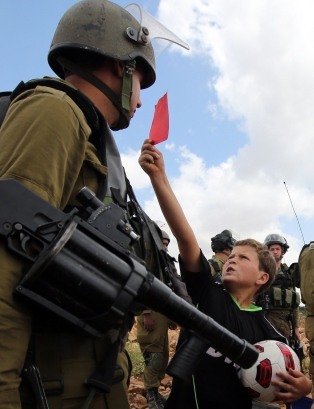 "A Palestinian boy shows a red card to an Israeli soldier during a rally to show their support for the Palestinian bid to vote the Israel Football Association (IFA) out of FIFA on May 29, 2015 in the West Bank village of Nabi Saleh near Ramallah. Israel welcomed the avoidance of an ""absurd situation"" after the Palestinian Football Association withdrew a motion to expel the Jewish state from FIFA.    AFP PHOTO / ABBAS MOMANI"